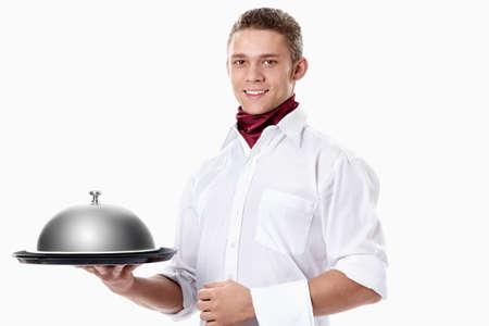 mesero: El joven camarero con una bandeja de cubiertos con una c�pula sobre un fondo blanco Foto de archivo