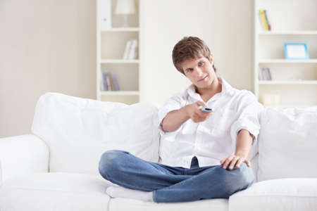 A young man switch TV channels at home photo