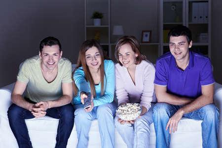 personas viendo tv: J�venes amigos atractivos ven televisi�n en casa Foto de archivo
