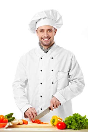 the knife: El joven cocinero corta verduras sobre fondo blanco Foto de archivo