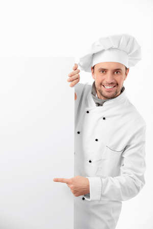 Le jeune chef souriant avec les panneaux d'affichage