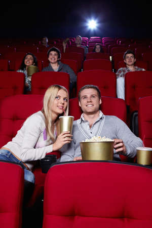 Attractive young people are watching movies in cinema photo