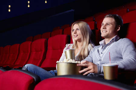 Attractive young couple looking at a movie theater photo