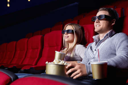 Attractive young couple in 3D glasses watching movies in cinema photo