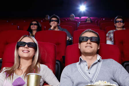 Attractive young people in 3D glasses watching a movie at the cinema photo