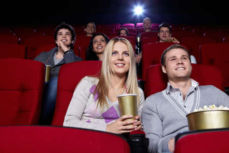 Attractive people are watching a movie at the cinema photo