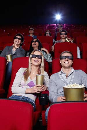 Personas sonrientes en gafas 3D viendo una pel�cula en el cine Foto de archivo - 9326608