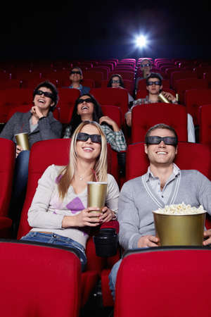 Smiling people in 3D glasses watching a movie at the cinema photo
