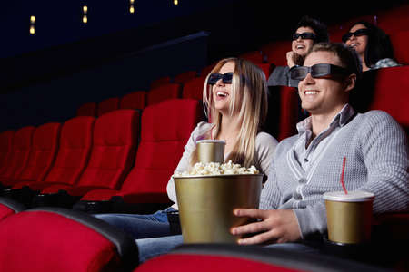 Laughing young people in 3D glasses watching a movie at the cinema photo