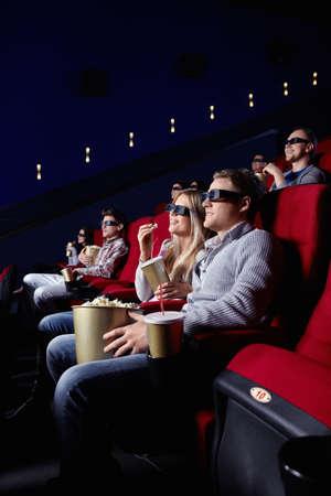Smiling people in 3D glasses in cinema