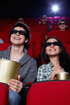 Laughing couple in 3D glasses in cinema photo