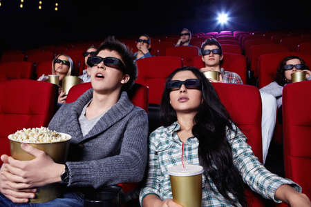 Young people in 3D glasses hard watching a movie at the cinema photo