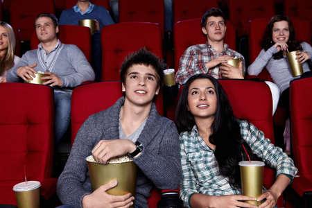 cinta pelicula: J�venes estrechamente est�n viendo una pel�cula en el cine Foto de archivo