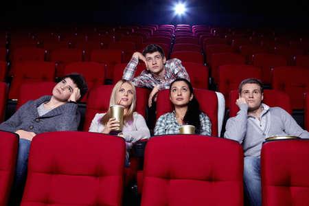 bored man: Soddisfatte ragazze e ragazzi annoiati, guardando un film al cinema