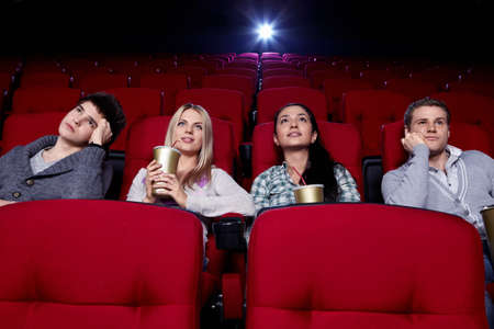 Satisfied girls and bored boys watching a movie at the cinema