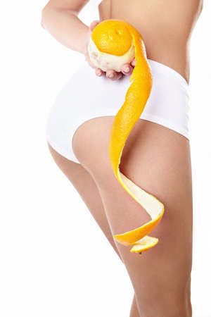 A young girl in underwear with an orange on a white background photo