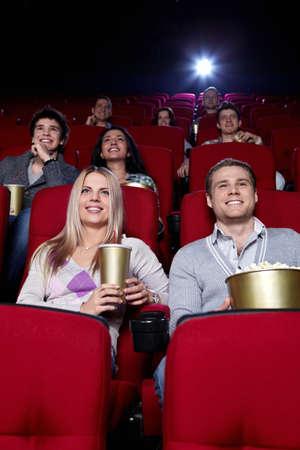 Sonrientes personas están viendo películas en el cine Foto de archivo - 9405175