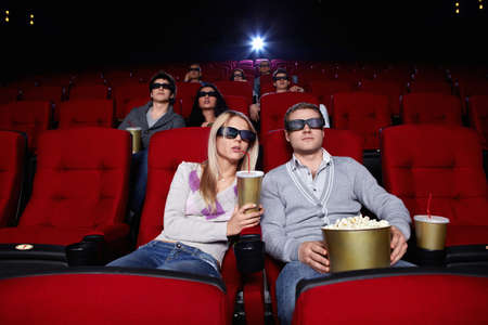 Young people watch movies in 3D glasses in cinema photo