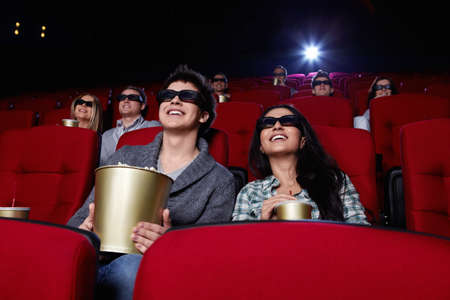 Funny people are watching a movie in 3D glasses in cinema photo