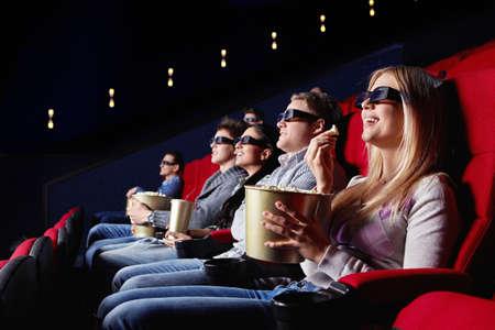 Smiling people in 3D glasses in cinema photo