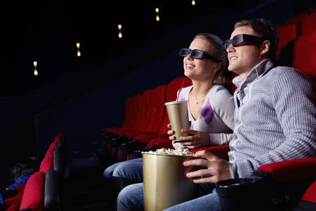Young couple watching a movie in 3D glasses in cinema Stock Photo - 9405166