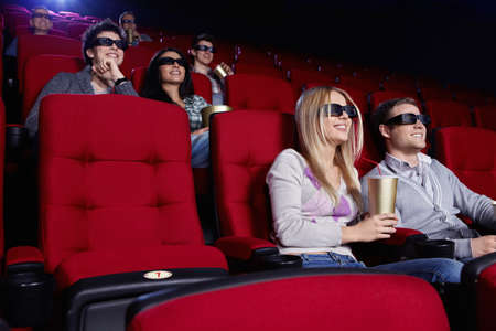 Smiling people watch movies in cinema photo
