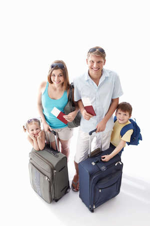 A happy family with their suitcases and passports to leave on a white background photo