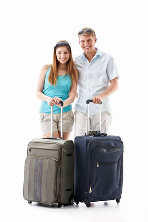 An attractive couple with their suitcases on a white background photo