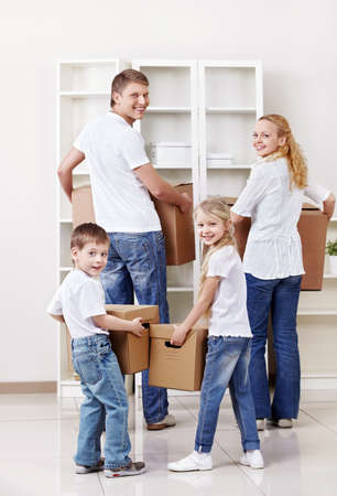 Family with cardboard boxes indoors photo