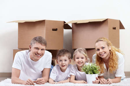 Families with children on the carpet against the backdrop of cardboard boxes photo