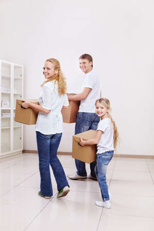 Parents with a child are cardboard boxes indoors photo