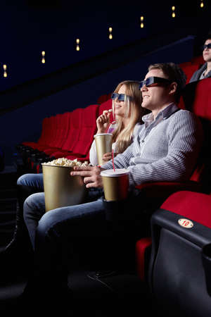 Young people in 3D glasses in cinema photo