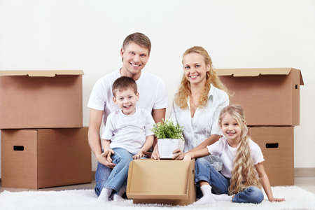 Families with young children unpack boxes photo