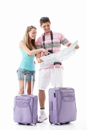 Attractive young couple with  suitcases looking map isolated photo