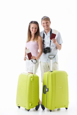 Attractive young couple with suitcases and passports isolated photo