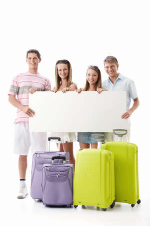 Young people with suitcases and empty billboard on a white background photo