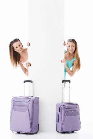 Young girls with suitcases and empty billboard on a white background photo