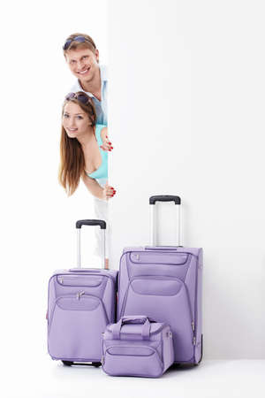Young couple with suitcases and empty billboard on a white background photo