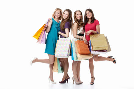 chicas de compras: Lindas ni�as con sus bolsas sobre un fondo blanco Foto de archivo