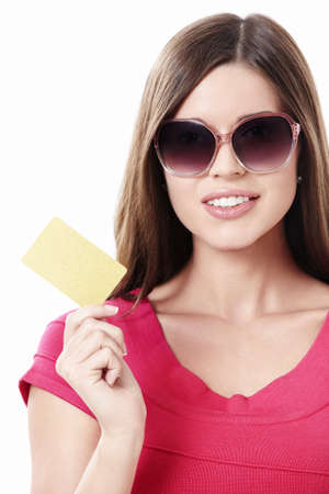 Young girl in sunglasses with a credit card on a white background photo