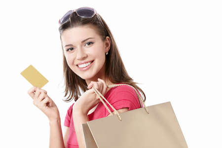 card payment: Young girl with a credit card and shopping bags isolated