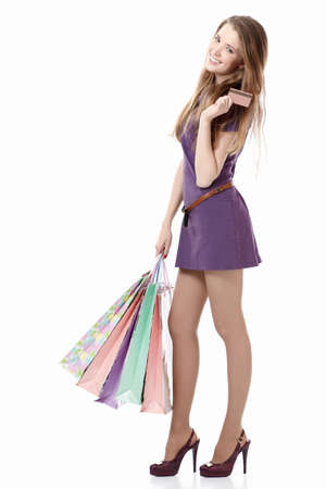 shopping card: Young girl with a credit card and shopping bags on white background