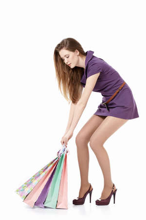 A young girl pulls bags on a white background Stock Photo - 9603023