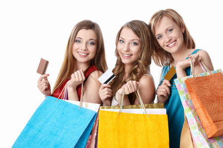 happy shopper: Attractive girls with bags and credit cards on a white background Stock Photo