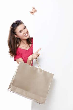 white paper bag: Una mujer joven con una bolsa de puntos para anunciar Foto de archivo