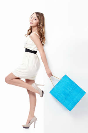 shopaholics: Young girl with a bag of flying on a white background