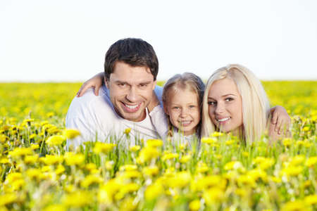 Happy young family in the dandelion field photo