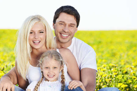 on pasture: A happy family with a child in a field Stock Photo
