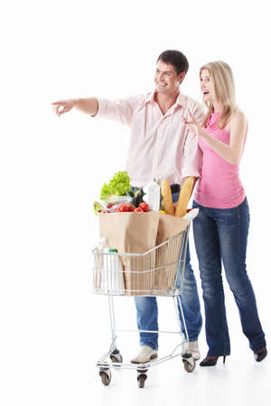 The happy couple with a cart with food on a white background Stock Photo - 9794407