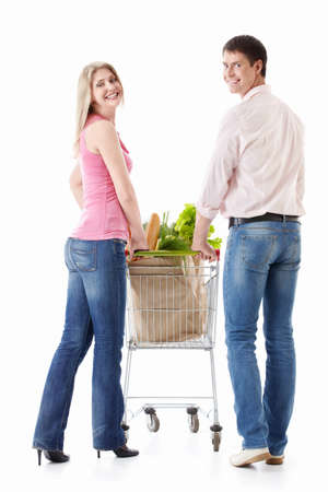 The happy couple with a cart with food on a white background photo
